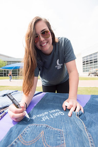 Sophia Zaner writes a supportive message on a pair of jeans during Denim Day, part of Sexual Assault Awareness Month.