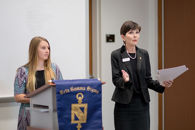 Logan Wiggen (left) and Dr. Sharon Polansky welcome guests to the Beta Gamma Sigma Induction Ceremony.