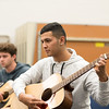 Student Thomas Lopez looks at sheet music while learning to play Jingle Bells in Basic Guitar I.