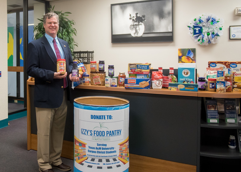 TAMUCC College of Liberal Arts Dean Mark Hartlaub poses next to the food donated to Izzy's Food Pantry.   Click on the link for more information on Izzy's Food Pantry: http://bit.ly/2GG9Ph4