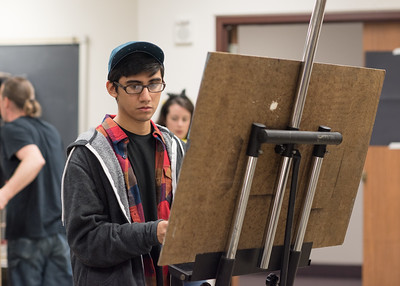 Student Jose Manrique sight measures a still life before starting his assignment in Drawing 1.