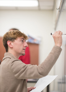 Student Kalon Melton works on an equation on the board during Minds and Machines.