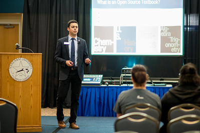 """Justin Bustos, President of the Student Government Association, gives a presentation on """"Free Textbooks-An Open Education Resource"""" in the Legacy Ballroom."""