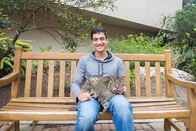Marcos Garcia sits on a bench with one of campus' friendly cats near Cat Alley.