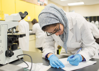 Student Danah Aljonenil works on her assignment during a Microbiology lab.