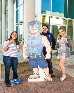 Magdalena Montez (left), Jaime Baza, and Shelby Fresier show off their support for Enrollment Management by posing next Izzy the Islander and passing out wristbands.