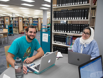 Mason Fitzwater (left) and Danah Aljunaidi work on their Microbiology reports in the Mary and Jeff Bell Library.