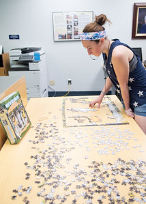 "Kayla Buchi completes a ""Where the Wild Things Are"" 1,000 piece puzzle at the Mary and Jeff Bell Library."
