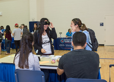 Sarah Pena tries on iTeam's vision impairment goggles during the Health and Wellness Expo.