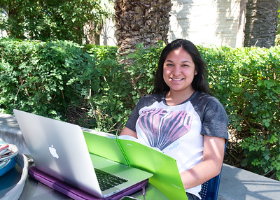 Noemi Dominguez works on her English assignments in the Hector P. Garcia Plaza.