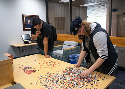 Richard Quiroz (left), and Diana Mojica unwind between classes by contributing to the Mary and Jeff Bell Library's community puzzle.
