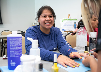 "Alanderia Cantu poses for a photo as she gets her nails painted yellow as part of ""Treat Yourself""at the University Center."
