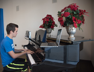 Louis Chavez practices on the piano in the University Center Tejas Lounge.