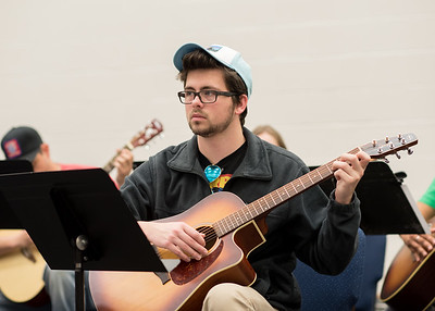 Student Dominic Dewar listens to instructions before playing in Basic Guitar I.