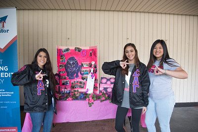 Sigma Lambda Gamma (via. @tamuccgammas) members Sofia Flores (left), Micaela Hernandez, and Ashley Ventura set up a table in the Breezeway for recruiting new members.