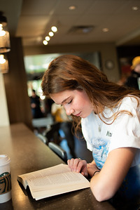 """Maggie Cook a freshman majoring in Education stops by the University's Starbucks cafe to read """"Tattooed Soldier"""" for her English 1301 class."""