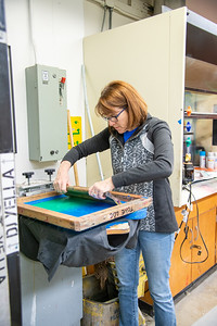 Professor Meg Aubrey floods a screen in a screen printing demo for the Student Art Association.