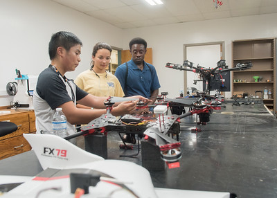 Vincent Nguyen (left), Christina Lee, and Darcy Houston review drones in the maintenance station during the UAS Field Day in Precision Farming.  View more photos: http://bit.ly/AG-UAS