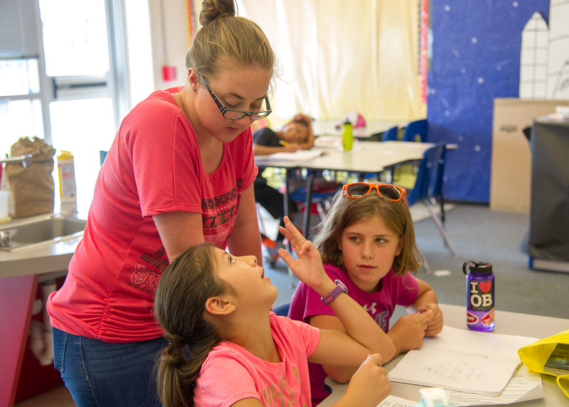 Gabriella DeLeon asks the Summer Writing Camp instructor about her homework.