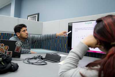 Vinrh Bod works with another student on an assignment in the Mary and Jeff Bell Library.
