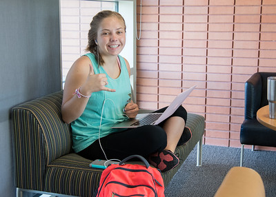 Islander student Megan Holley takes a break from working on an assignment to throw a shaka in the O'Connor Building.