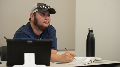 Jakob Vasquez takes notes during a lecture in Dr. Armand Picou's Investments class.