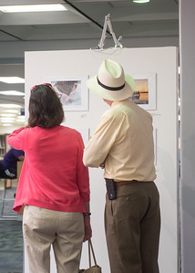 Attendees view images submitted at the Islander Cell Phone Photography Show at the Mary and Jeff Bell Library.