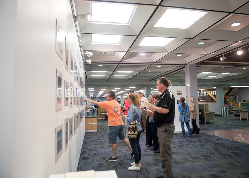 Students and staff view images submitted for the Islander Cell Phone Photography Show at the Mary and Jeff Bell Library.