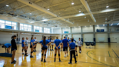 The Islanders women's volleyball coach deliberates with his team.