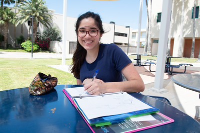 Ilsa Rodriguez enjoys the cool breeze while working on her assignments in the Center for Instruction's patio.