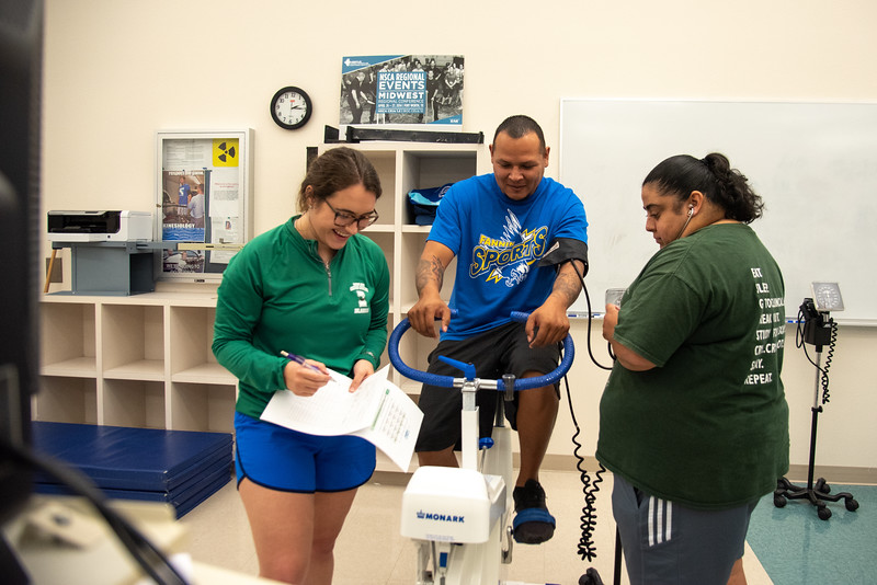 Hannah Waldrop (left), and Dany Escobar (right) collect data from Chris Dominguez for their Aerobic Power lab during a Kinesiology lab session.