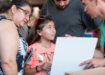 Anna Amaya (right) and Alana Martinez, age 9, learn about shark tagging at one of the booths during Shark Week Live at Brewster Street Ice House.