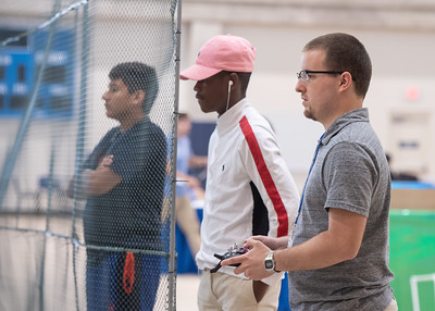 Lead counselor Richard Q. Ingolia (right) helps one of the teams use a drone to pick up objects during the UAS Summer Institute.