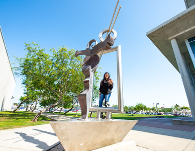 Islander student Hazel Puga poses for a creative photo with the statue between the Center for the Arts and Bay Hall.
