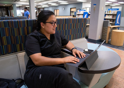 Cynthia Faragoza works on her assignments in the Mary and Jeff Bell Library's lobby.