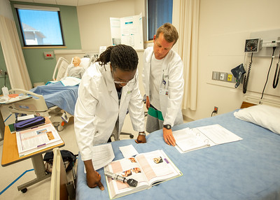 McAllen Waobikeze (left) and Steve Wright partner up as they conduct a physical examination lab with one another at Islander Hall's upstairs mock hospital