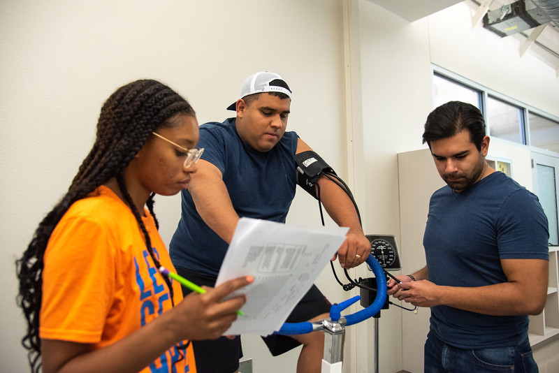 Emari Johnson (left), and Jesse De La Cruz (right) collect data from Ryan Ramon  for their Aerobic Power lab for their Kinesiology class lab session.