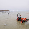 """Record-Eagle File Photo<br /> Jeremiah Steffen, on tractor, along with his NorthShore Dock co-workers, remove docks for the winter Tuesday, October 16, 2012 from West Grand Traverse Bay. """"It's a lot easier than pushing them in,"""" Steffen said about removing the docks."""