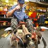 Record-Eagle/Dan Nielsen<br /> Marc Fleis peers inside the gearbox of a broken rototiller.