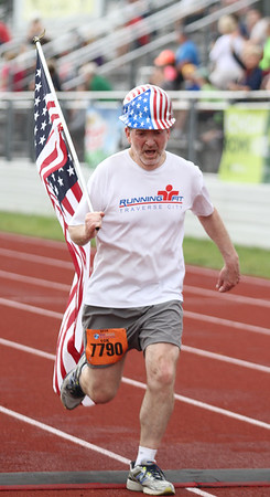 Record-Eagle/James Cook Dan Lantis carries an American flag across the 10K finish line at Saturday's Bayshore Marathon.