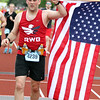 Record-Eagle/James Cook Brian Jirous holds an American flag as he crosses the finish line in Saturday's Bayshore Half Marathon.