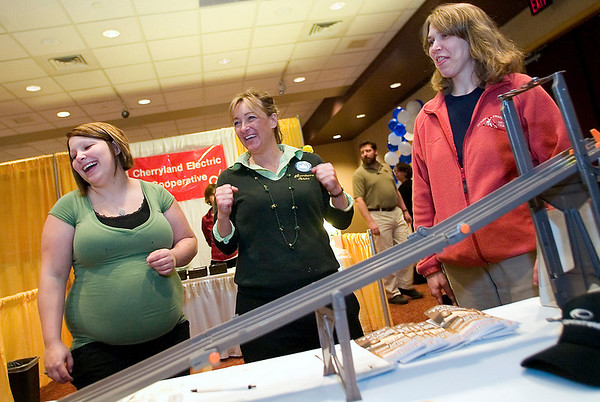 Record-Eagle/Jan-Michael Stump<br /> From left, Joan Culvertson, of Beulah; Northern Auto and Tire owner Zela Gray; and Betsy Schaub, of Thompsonville, watch their cars race down a track at the business' booth at the Benzie Chamber of Commerce Expo 2010. The Tuesday event featured about 50 vendors at the Crystal Mountain Resort and Spa conference center.