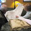 Record-Eagle/Jodee Taylor<br /> Tim Carroll and Mary Rademacher look at the christening dress Rademacher found at a garage sale. The dress came from the Wilhelm side of Carroll's family. A pillow depicting the family home is on the table.