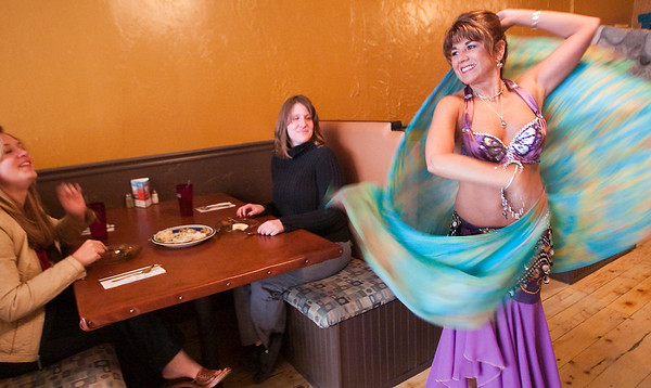 """Record-Eagle/Douglas Tesner<br /> Carmen Torres, a Middle Eastern dancer known as """"Amaya,"""" dances for customers Emma and Megan Schrider at the new downtown Zakey restaurant. Torres also dances at Zakey's Three Mile location, which opened two years ago."""