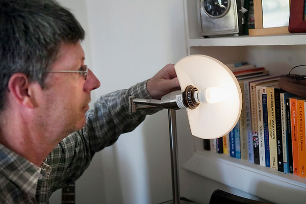 Record-Eagle/Douglas Tesner<br /> Jon Roth checks a compact florescent light bulb he uses to help his family reduce its carbon footprint.