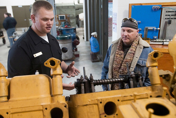 Record-Eagle/Douglas Tesner<br /> Cadet Justin Reinert gives Lars Bickford some information on maintaining one of the engines during an open house at the Great Lakes Maritime Academy. Visitors met cadets, faculty and staff and toured the academy.