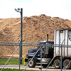 Record-Eagle/Jan-Michael Stump<br /> A pile of wood chips sits near the entrance as a truck brings another delivery to Cadillac Renewable Energy.
