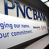 Record-Eagle/Douglas Tesner<br /> Connie Nunemaker, assistant vice president of National City Bank Grand Traverse Branch,  stands by the new sign the bank will unveil next Monday when they officially make the conversion to PNC Bank.