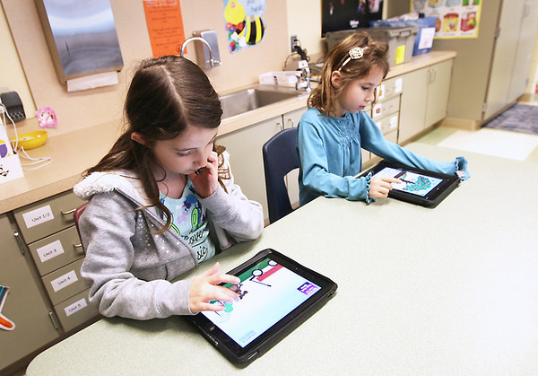 Record-Eagle/Keith King<br /> First-grade students Aisha Smith, left, and Mary Palamara, demonstrate educational programs on iPads at Old Mission Peninsula School.