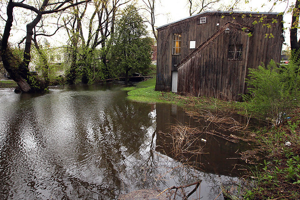 Record-Eagle/Keith King<br /> High water levels are visible on Kids Creek behind Latte-Dah on West Front Street on Friday after rain showers.